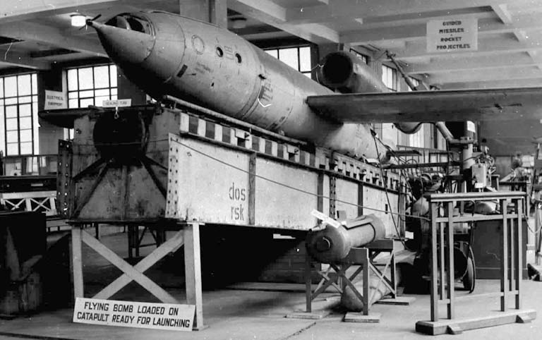 A V-1 sits on a lunch rail in what appears to be a work shop.